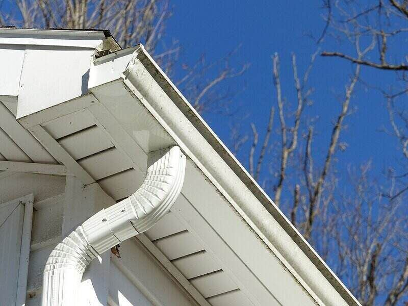 Looking up at gutters and downspout along the top of a house