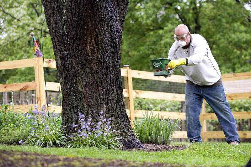 Man using a manual fertilizer for his yard