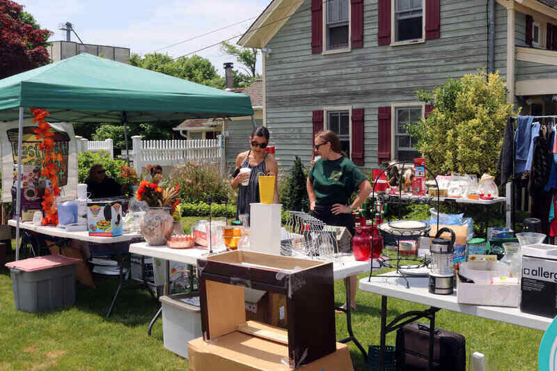 two women standing behind a table looking at items in a yard sale