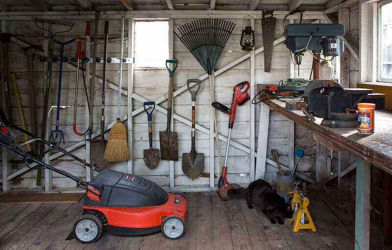 Inside a tool shed with garden tools and supplies hanging in an organized manner on the back wall, with a lawn mower on the floor