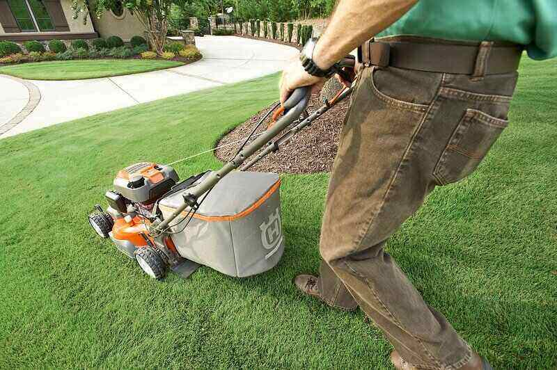 man mowing the lawn with an orange lawn mower