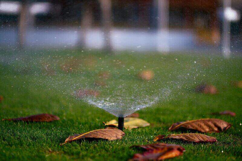 automatic lawn sprinkler on and surrounded by leaves in the yard